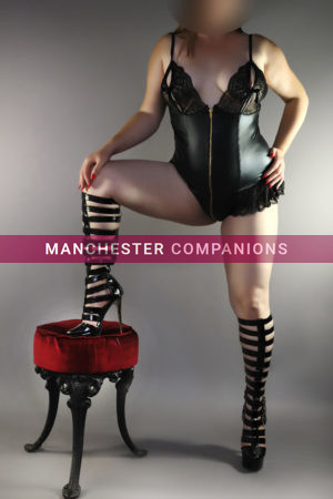 Isabelle wearing a tight black pvc outfit with knee high black strappy boots