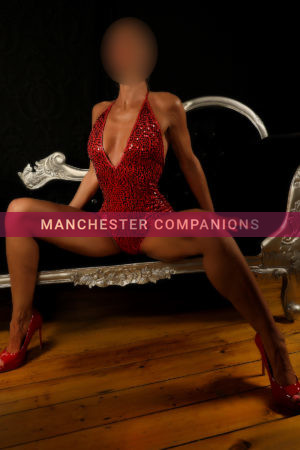 Naomi sat astride on a black sofa wearing a sexy sparkly red body suit and red stilettos