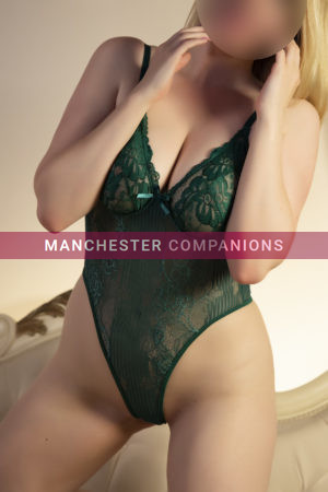 Samantha against a cream back ground hands on neck wearing a dark green lace bodysuit