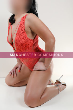 Sadie kneeling against a white background wearing a tight fitting coral coloured lace body and silver heels