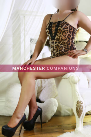 Nina sat in a boudoir wearing an animal print body and very high heels