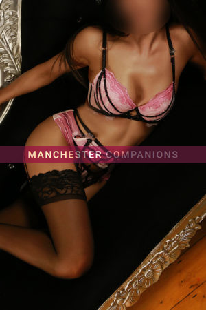 Alisha lay on a black chais long in a beautiful pink and black lingerie set
