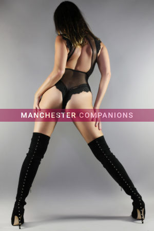 Suzi facing a grey wall legs apart wearing a black thong bodysuit and knee high boots