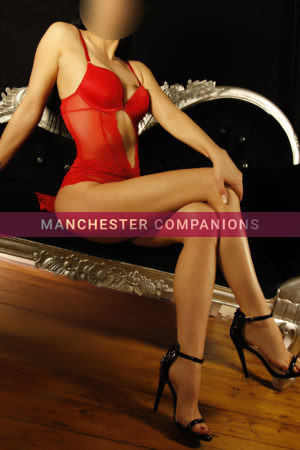 Kayleigh sat on a black chais long legs crossed in red bodysuit