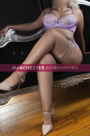Annabelle sat on a black chais long legs crossed in lilac lingerie and nude heels