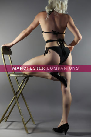 Polly stood up with one leg on stool wearing black underwear with bare legs and high heels