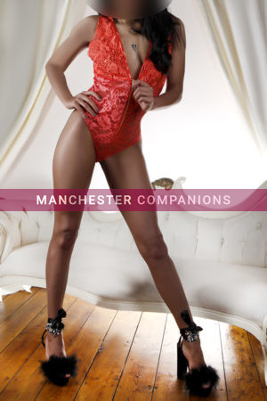 Carmel stood up and looking cheeky in front of a white couch wearing a lacey red body and black heels