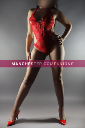 Jade stood up wearing sexy lace red lingerie and red heels against a shaded background