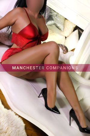 charlotte sitting on a white chair wearing her red crop set with high heels