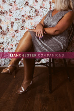 Mel sat down wearing a silver evening dress with silver heels and nude stockings against a flowery background