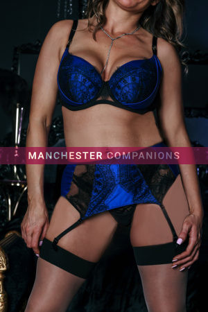 Close up of Jamie's cleavage stood up wearing a blue satin 2 piece lingerie and black stockings