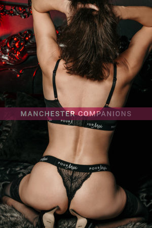Rear view of Vanessa wearing black gym lingerie with black stockings against a dark background